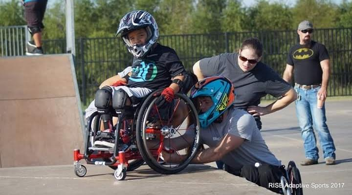 Blake Simpson helping a young child repair his wcmx wheelchair at a RISE Adaptive Sports event in Texas